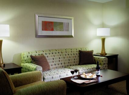 Table With Room Service, Armchair, Illuminated Lamps, and Wall Art Above Sofa in Living Room Suite