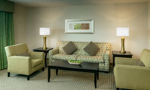 Window With Green Drapes, Two Armchairs, Illuminated Lamps on Side Tables, and Wall Art Above Sofa in  Suite Living Room