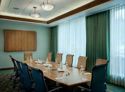 Seating for 12, Water Pitchers, Drinking Glasses, and Notepads at Connectivity Table in Boardroom With Media Cabinet, and Windows With Long Drapes