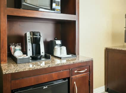 Detailed View of Hospitality Center With Mini-Fridge, Keurig, Sink, and Microwave