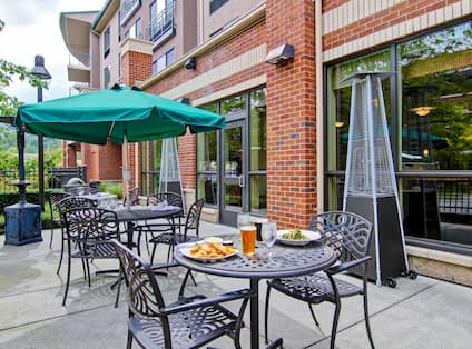 Green Umbrella, Table With Plates of Food and Drinks, Chairs, and Heat Lanterns on Patio by Hotel Exterior