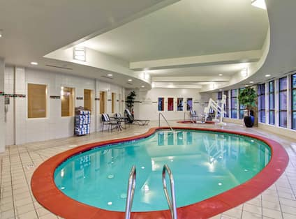 Indoor Swimming Pool and Whirlpool With Towel Station, Table, Chairs, Lounger, and Windows