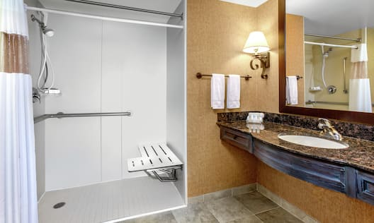 Bathroom with roll-in shower and vanity with sink