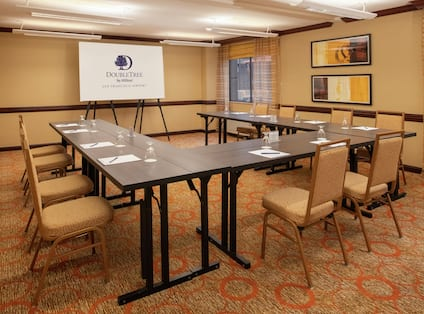 a u-shaped table facing a presentation screen in a meeting room