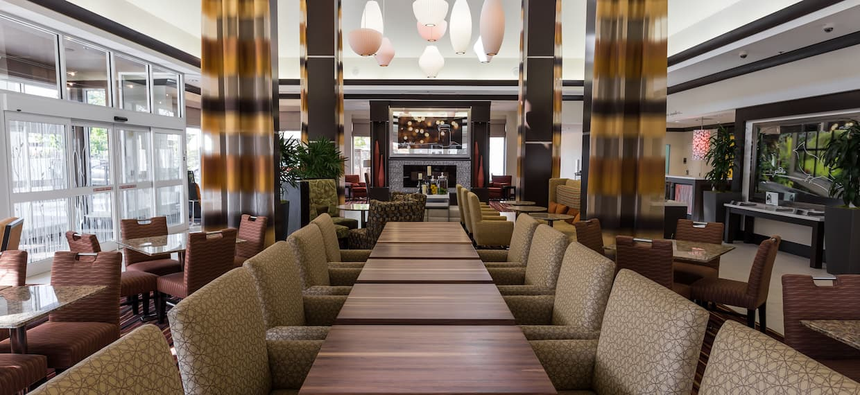 Large Windows, Tables, Chairs, and Long Drapes in the Garden Grille and Bar With View of Fireplace in Background