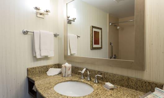 Wall Art, and Bathtub Reflected in Large Vanity Mirror, Sink, Fresh Towels, and Toiletries in Standard Bathroom
