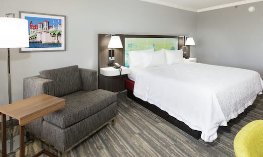 King Bed and Soft Lounge Chair with Side Table in Guest Room