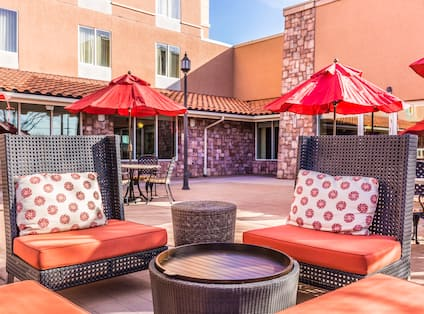 View of Outdoor Patio Area with Tables Chairs and Umbrellas