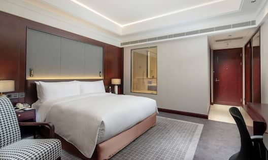 Bed in room with desk and chair