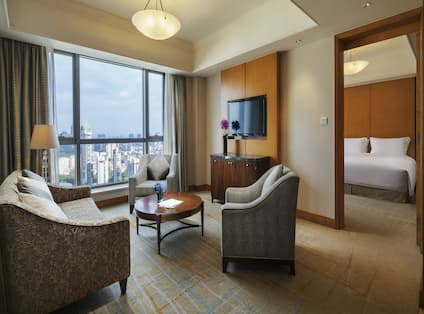 Guest Suite Lounge Area with Sofa, Armchairs, Coffee Table, City View and Wall Mounted HDTV