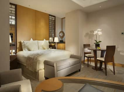 One Bed Guest Suite Bedroom with Armchair, Coffee Table and Sitting Table