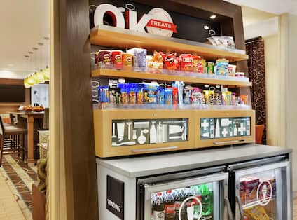 Packaged snacks on shelves and refrigerated, counter with chairs