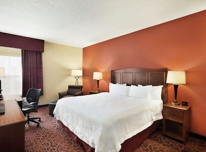King bed, TV, chair, desk by window