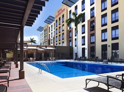 Outdoor Pool with Chaise Lounge Chairs and View of Hotel Exterior and Signage on a Sunny Day