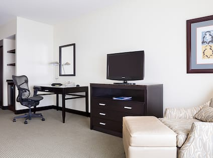 Work Desk, TV, Wall Art and Soft Chair with Ottoman in Corner