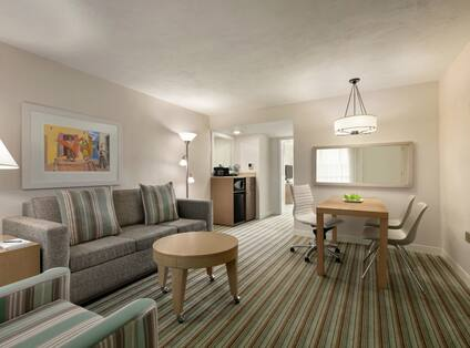 Spacious living area in suite featuring sofa, TV, dining table, and wet bar.