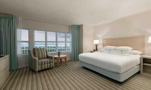 Spacious private bedroom in presidential suite featuring comfortable king bed, seating area, and large window with beautiful outside view.