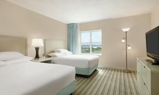 Bright private bedroom in suite featuring two comfortable double beds, TV, and beautiful outside view.