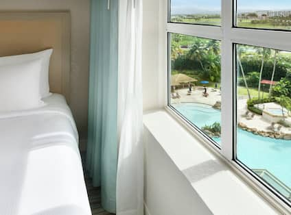 Bright bedroom in suite featuring beautiful view overlooking the large hotel pool, hot tub, and bar.