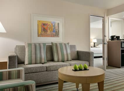 Spacious living area in two bedroom suite featuring comfortable seating area and wet bar.
