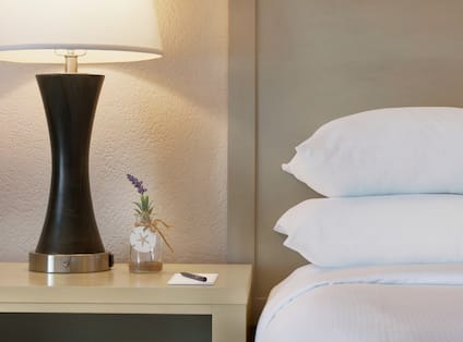 Bedside table in suite featuring notepad with pen and beautiful lavender in a vase.