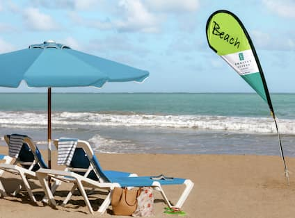 Beautiful private beach featuring lounge chairs, towels, and umbrella.