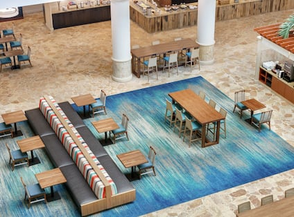 Aerial view oh hotel breakfast area featuring ample seating, coffee station, and complimentary buffett.