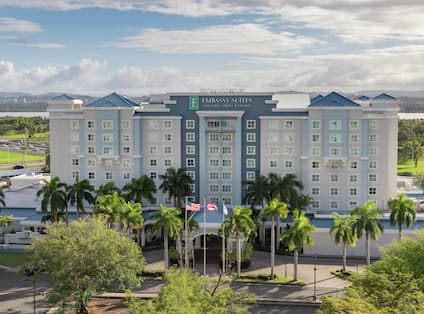 Aerial view of Embassy Suites hotel surrounded by beautiful palm trees, mountains, and blue sky.
