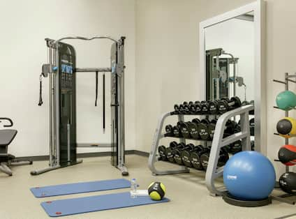 Convenient on-site fitness center featuring work out machines, free weights, and yoga mats.