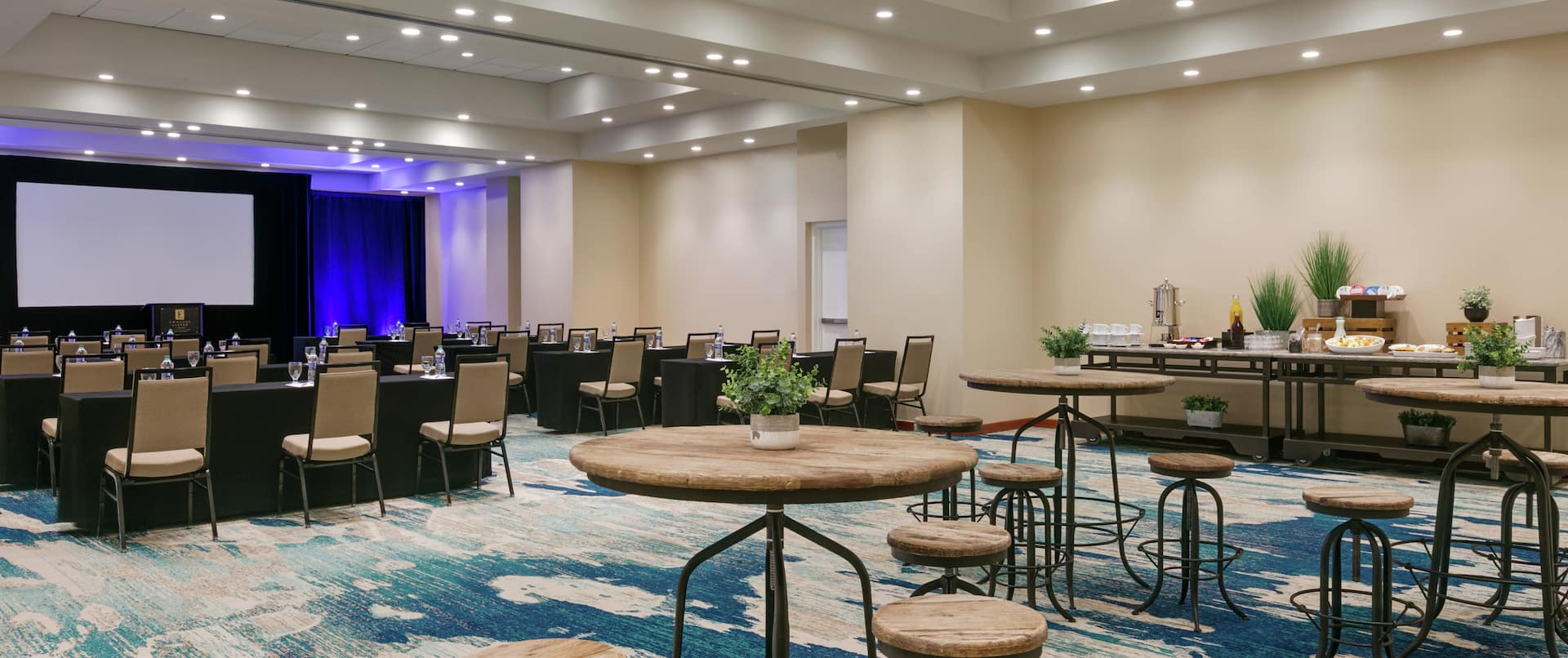 Spacious Tropico meeting room featuring classroom setup, social seating area, and refreshment station.