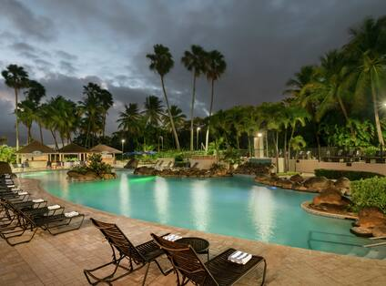 Beautiful pool area at night featuring ample seating, glowing underwater lights, and pool bar.
