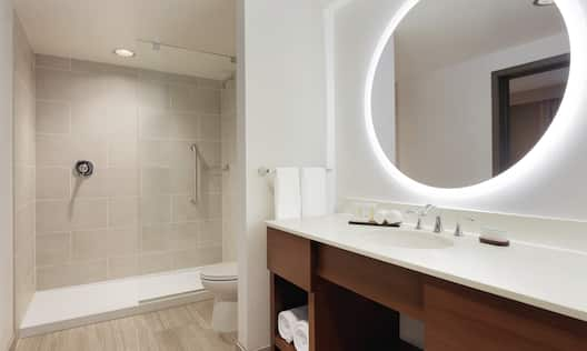 Standard Bathroom Vanity with Round Mirror and a Shower