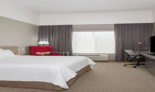 King-Sized Bed Facing TV in Standard Bedroom with Large Window