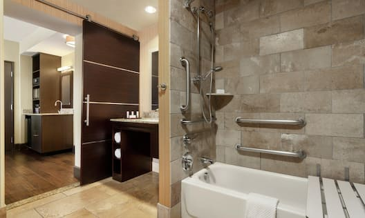 Accessible Guestroom Bathroom with Bathtub, Shower, and Seat