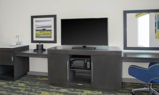 Wet Bar, TV on Cabinet Holding the Microwave and Mini Fridge, next to Desk and Chair