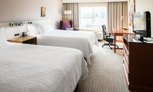 Illuminated Lamp and Bedside Table Between Two Queen Beds, Armchair,  Illuminated Floor Lamp, Window With Open Drapes, Work Desk, and TV in Guest Room