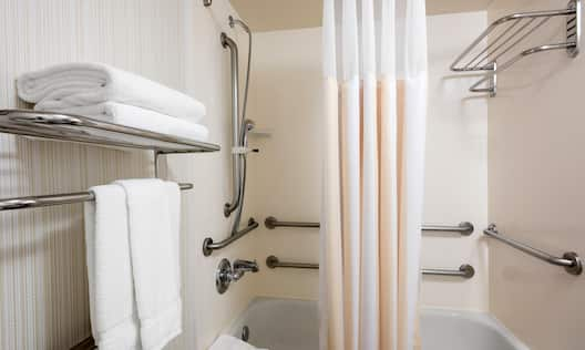 Fresh Towels and Bathtub WIth Grab Bars, SHower Curtain, and Handheld Showerhead in Accessible Bathroom