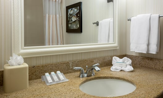 Shower Curtain and Wall Art Reflected in Vanity Mirror, Sink, Fresh Towels and Toiletries in BAthroom