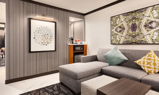 King Premium Suite Living Room with Couch, Microwave, Fridge and Entry to Bedroom