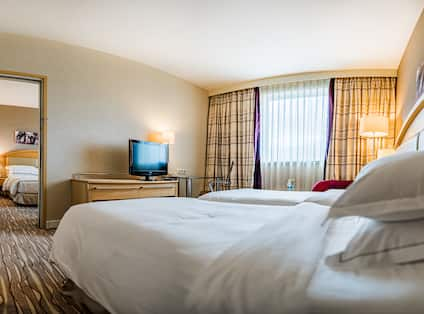 Family Suite Bed View with TV and Cabinet Angle 3