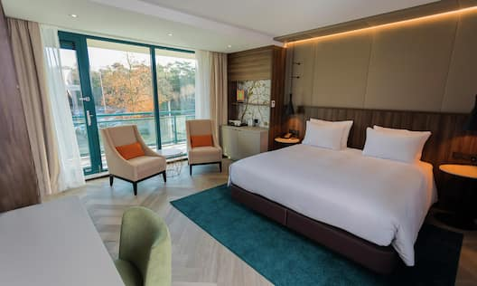 King Deluxe Guestroom with Bed, Lounge Area, Work Desk, and Outside View