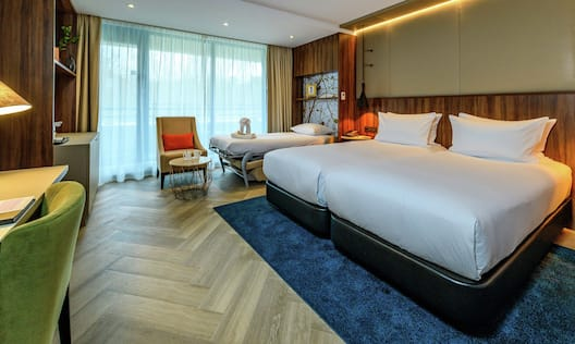 Twin Deluxe Guestroom with Two Beds, Sofa Bed, Lounge Area, and Work Desk