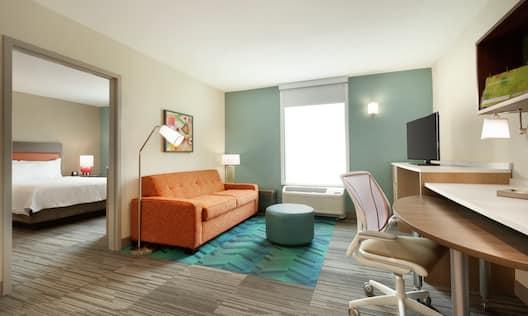 One Bedroom Queen Bed Suite Living Room with Open Doorway to Bedroom