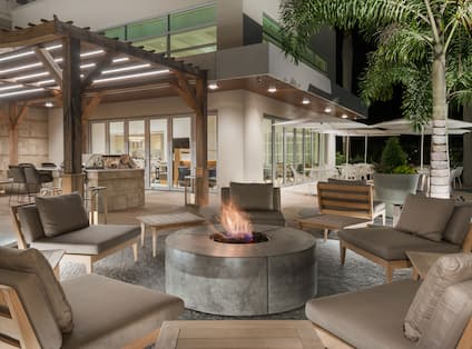 Night View of Outdoor Fire Pit Surrounded by Large Lounge Chairs and Tables with Umbrellas