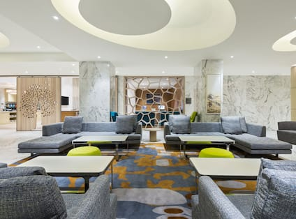 Four Large Grey Sofas with Square Tables and Two Yellow Ottomans in Lobby Seating Area
