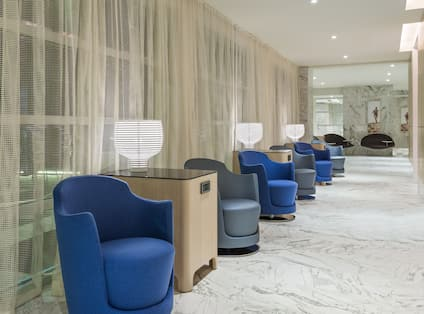 Blue and Grey Chairs in Hallway and Just Outside of Meeting Room With Draped Windows and Tall Square Tables