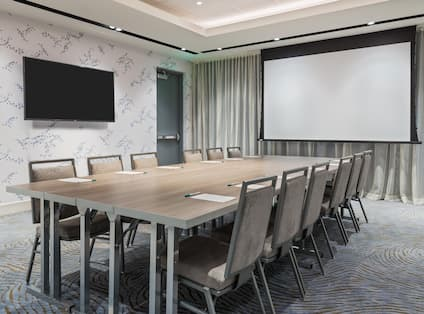 Boardroom-Style Setup With TV, Presentation Screen, and Seating for 12 people.