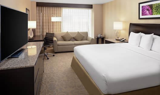 Sofa in Guest Room with Large Bed Desk and HDTV