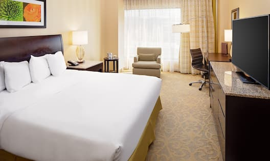 Guest Room with Large Bed Desk Armchair and HDTV