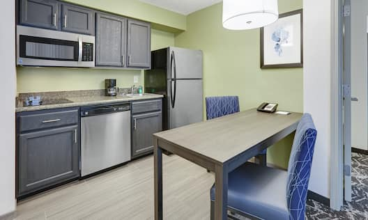 Guest Suite Kitchen Area with Refridgerator, Dishwasher, Microwave, Two Chairs and Table